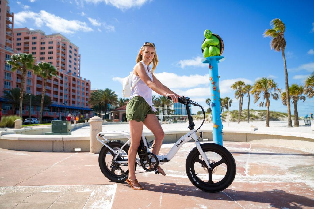 Blonde woman in a white tank top and green shorts pauses for a photo while riding her electric bicycle by Ride Scoozy.