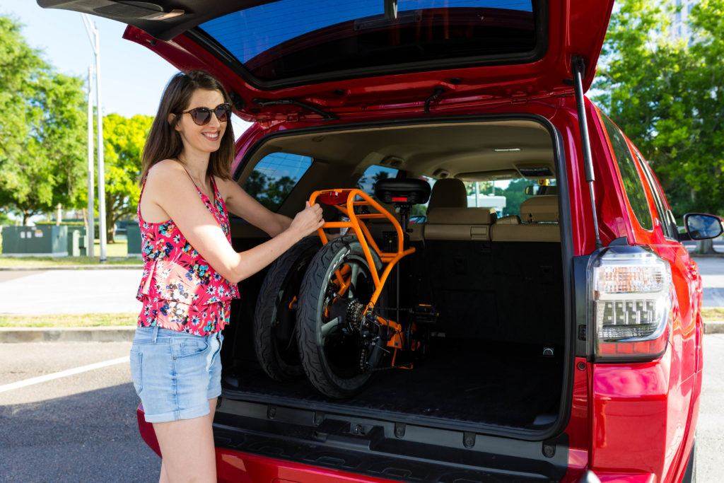 Brown haired woman wearing shorts and a tank top opens the trunk of her SUV to get out her Ride Scoozy electric bicycle.