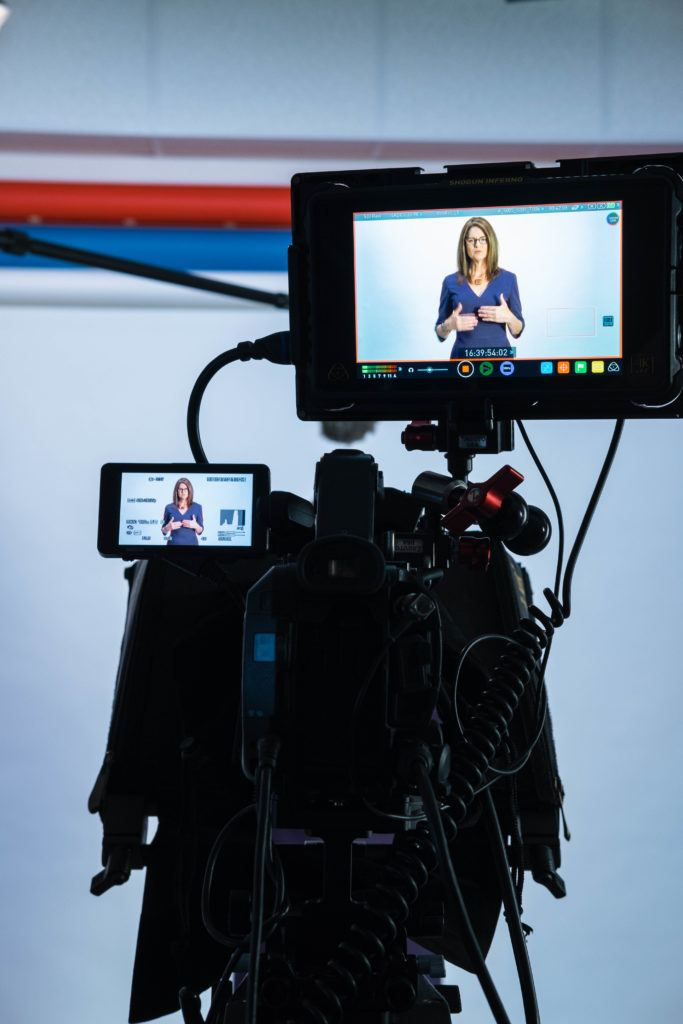 A picture of the back of a video production camera looking at Amanda Donnelly, DVM, standing in front of a white background.